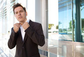 Businessman standing by a modern glass office — Stock Photo