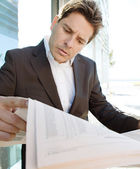 Businessman standing by a modern office building — Stock Photo