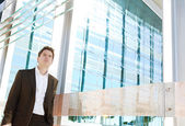 Successful businessman walking by a modern glass office — Stock Photo
