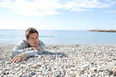 Man sitting down on the shore — Stockfoto