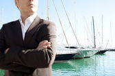 Businessman standing by a luxurious yachts — Stock Photo