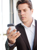 Business man holding a smart phone — Stock Photo