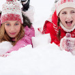 Two women laying down together on white snow — Stock Photo #42539445