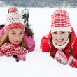 Two women laying down together on white snow — Stock Photo #42539663