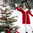 Girl decorating Xmas tree — Stock Photo