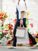 Woman walking passed  flowers market — Stock Photo