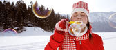 Vrouw blazen van zeepbellen buitenshuis — Stockfoto