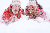 Two women laying down together on white snow — Stock Photo