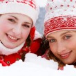Two women laying down together on white snow — Stock Photo #42540157