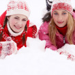 Two women laying down together on white snow — Stockfoto