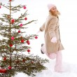 Girl decorating Xmas tree — Stock Photo