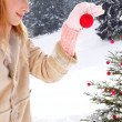 Woman decorating a Christmas tree — Stock Photo