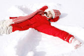 Woman laying down on the snow — Stockfoto