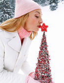 Woman kissing a  Christmas tree — Stock Photo