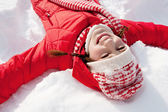 Woman laying down on the snow — Stock fotografie