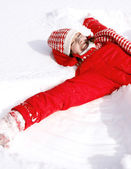 Woman laying down on the snow — ストック写真