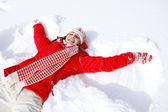 Woman laying down on the snow — 图库照片