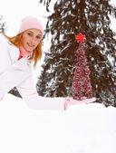 Woman balancing  Christmas tree — Stock Photo