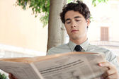 Businessman reading a financial newspaper — Stock Photo