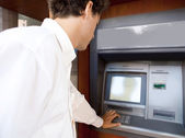 Businessman using an atm machine — Stock Photo