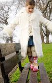 Girl  walking  on  bench — Stock Photo