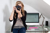Woman photographer taking a photograph — Stock Photo