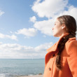 Woman facing the sea and breathing fresh air — Stock Photo #48318193