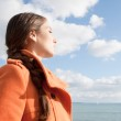 Woman facing the sea and breathing fresh air — Stock Photo #48318389