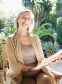 Woman sitting at a table in her home garden — Stock Photo