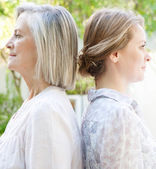 Daughter with her mother standing back to back — Stock Photo