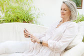 Woman lounging on a white sofa — Stock Photo