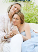 Daughter and her mother lounging together on a sofa — Stock Photo
