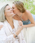 Daughter kissing her mature mother — Stock Photo
