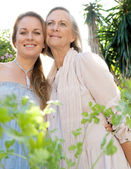 Mother and daughter standing in home garden — ストック写真