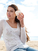 Woman holding a sea shell — Stock Photo