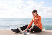 Woman sitting down by the ocean — Stock Photo