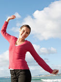 Woman feeling happy and raising her arms — Stockfoto