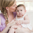 Mother holding and kissing her baby girl — Stock Photo #48322201