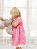 Girl child playing with  teddy bear — Stock Photo