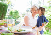 Grand child boy kissing grandmother — Stock Photo