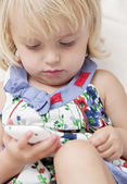 Infant girl holding a smartphone — Stock Photo