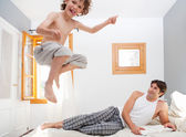 Child is jumping on bed near Father — Stock Photo