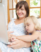Pregnant mother and infant daughter with laptop — Stock Photo