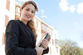 Businesswoman standing near classic office buildings — Stock Photo