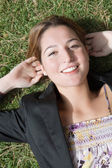 Woman laying down on green grass — Stock Photo