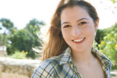 Woman smiling at the camera in a park — Stock Photo