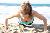 Woman doing push ups exercises on the beach — Stock Photo