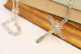 Catholic religious books with a silver praying rosary — Stock Photo