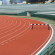 Hurdle on red running track — Stock Photo