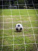 Old soccer ball on field — Stock Photo